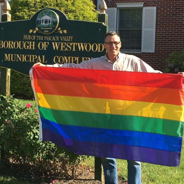 Westwood Mayor John Birkner holds a rainbow flag.