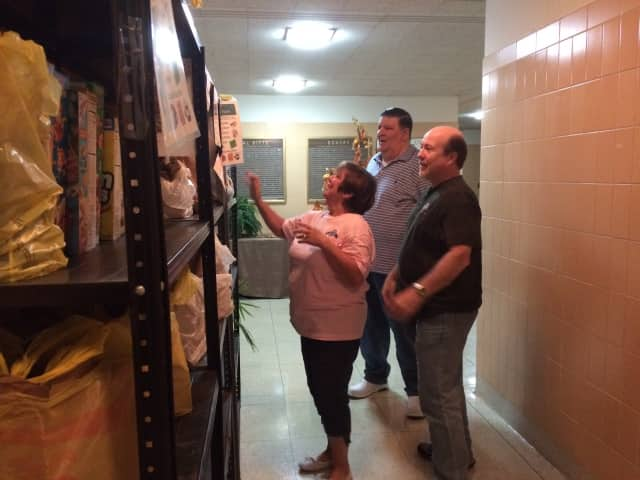 Volunteers Jackie Catti, Tom Mulcahy and Al Catti take a look at the food shelves at Our Lady of Perpetual Help Church in Oakland Friday, Oct. 9. The food donations are part of Bart's Pantry.