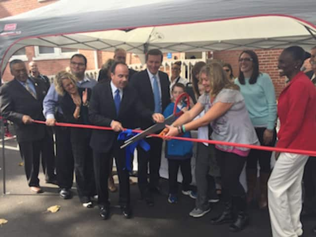 Bridgeport Mayor Joe Ganim, left, helps members of the late Jay Brothers family, cut the ribbon for the new Jay Brothers Unified Resource Center in Bridgeport. It helps ex-convicts turn their lives around.