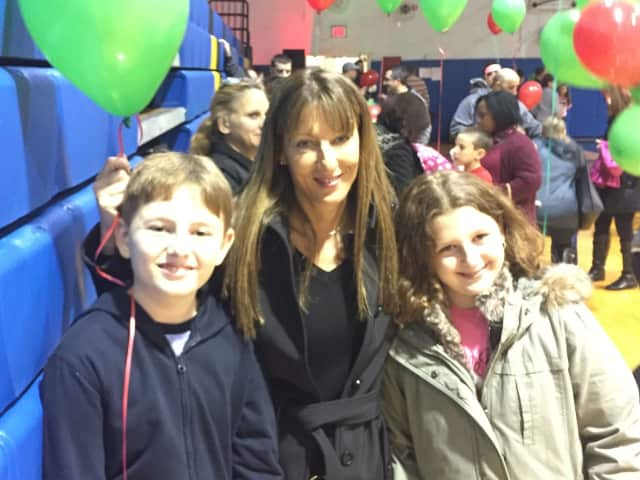 Regina Barrale stands with her children, Nicholas and Nina, in the Saddle Brook High School gym.