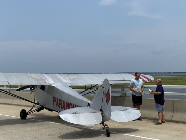 Landon Lucas (in blue) landed his banner plane in Ocean City Monday afternoon.
