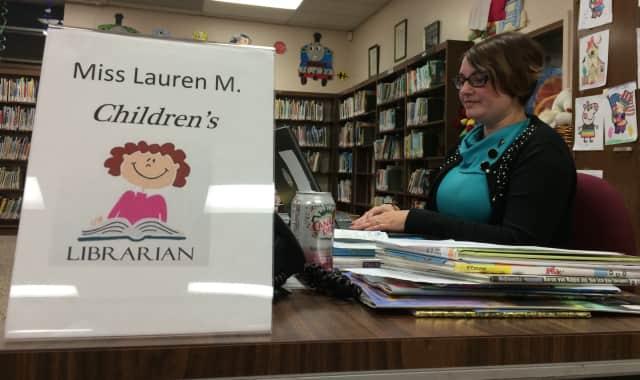 Lauren Magielnicki, new children's librarian in Garifled, works at her desk.