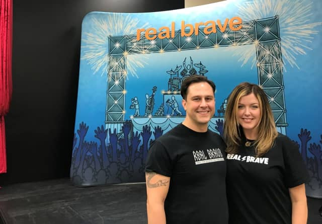 Daniel and Melissa Powers stand in front of the stage at Real Brave in Oakland.