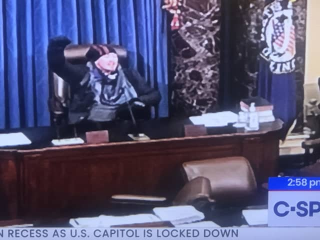 One of the protesters who stormed the Capitol building took to the dais in the chamber.