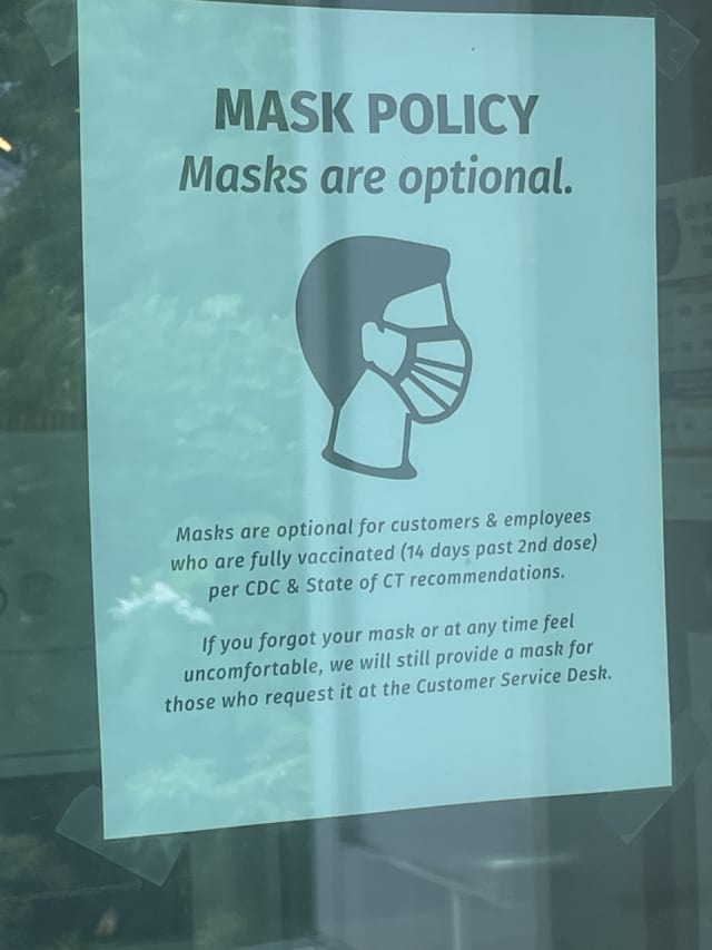 A sign posted at a store stating its mask policy, saying masks are optional for those fully vaccinated for COVID-19.
