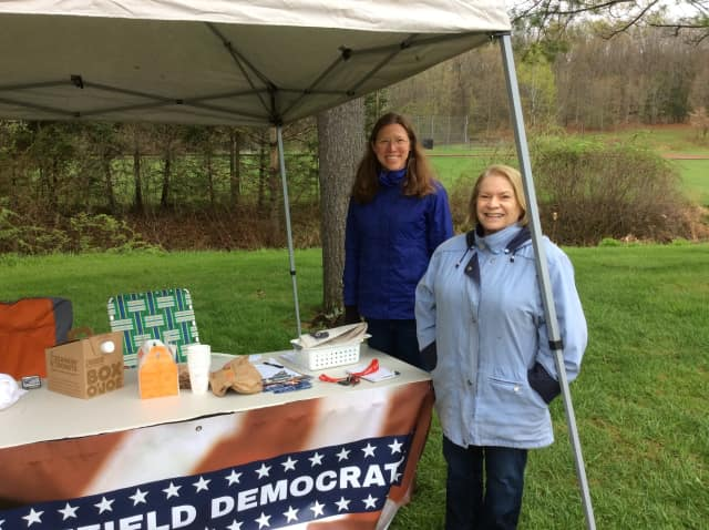 Eileen Koch and Susan Amlung of the Brookfield Democrats brave the chilly rain to offer information at the polling place at Huckleberry Hill Elementary School on Tuesday.