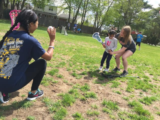 Saddle Brook High School varsity lacrosse players Kayla Chowdhury and Karissa Quimby give a young player some pointers. The team will hold a car wash fundraiser May 7.