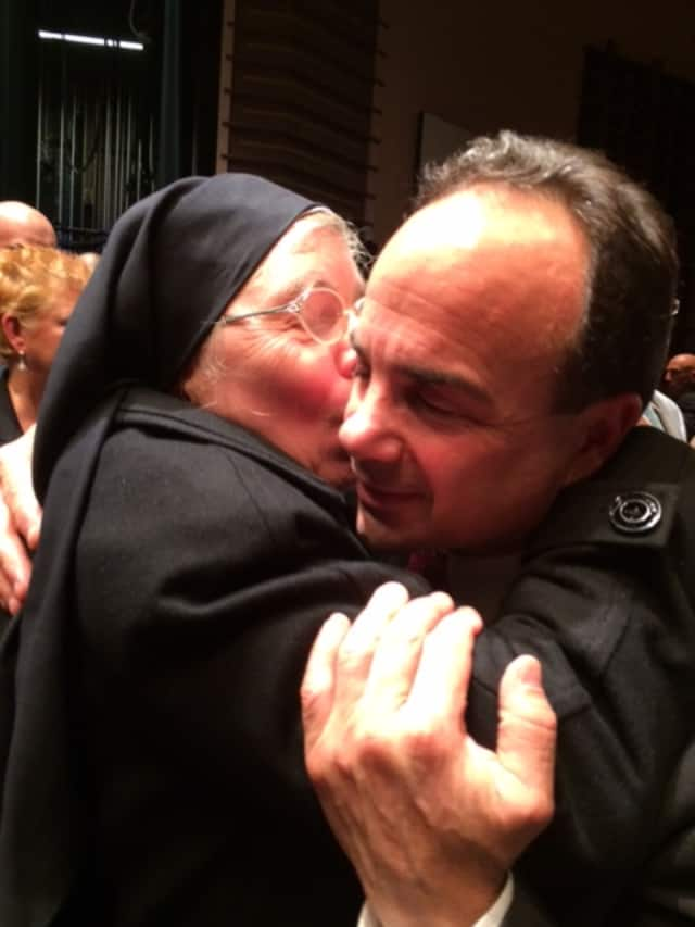 Bridgeport Mayor Joseph P. Ganim gets a kiss on the cheek from a fan at his swearing-in ceremony.