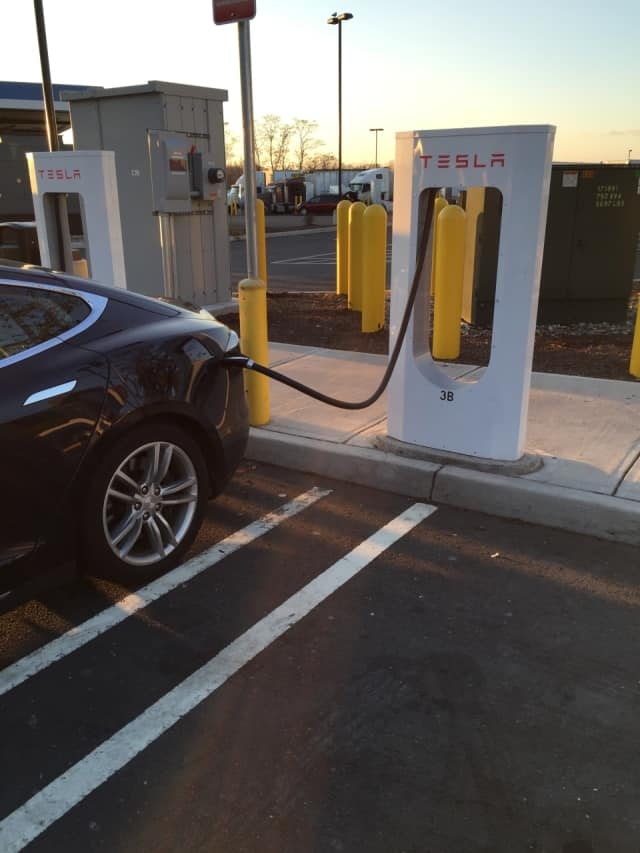 A Tesla charges up at an area station.
