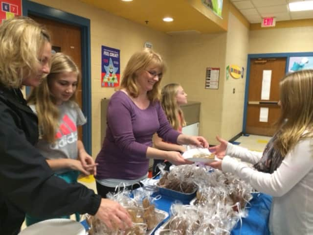 Stacie Rich, Mackenzie Rich, Dawn Kascak and Aubrie Rich pass out volunteer at the Eli Whitney School Holiday Social with Grace Kascak (r).
