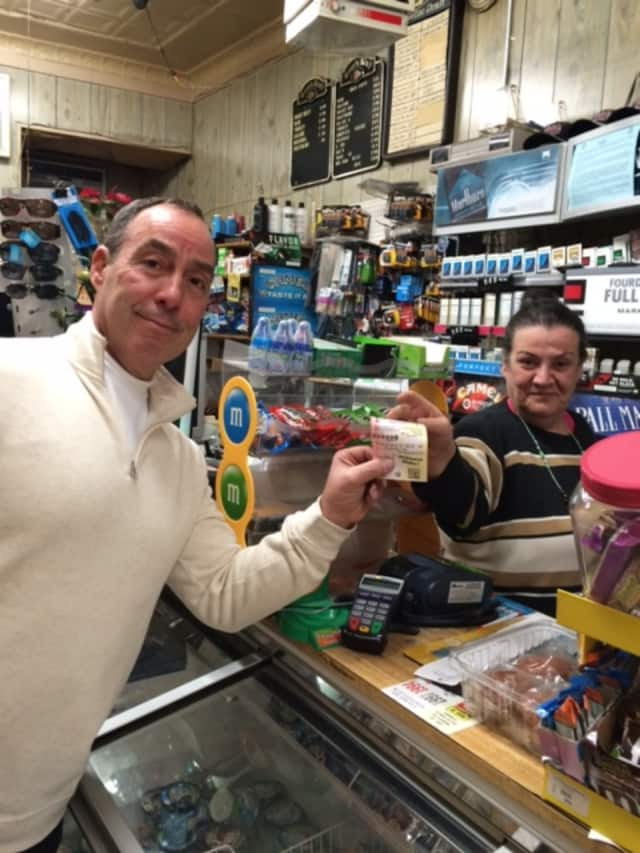 Bill John of Trumbull buys his Powerball ticket Thursday from Nada Ghalayini at Nick's Grocery in Bridgeport.