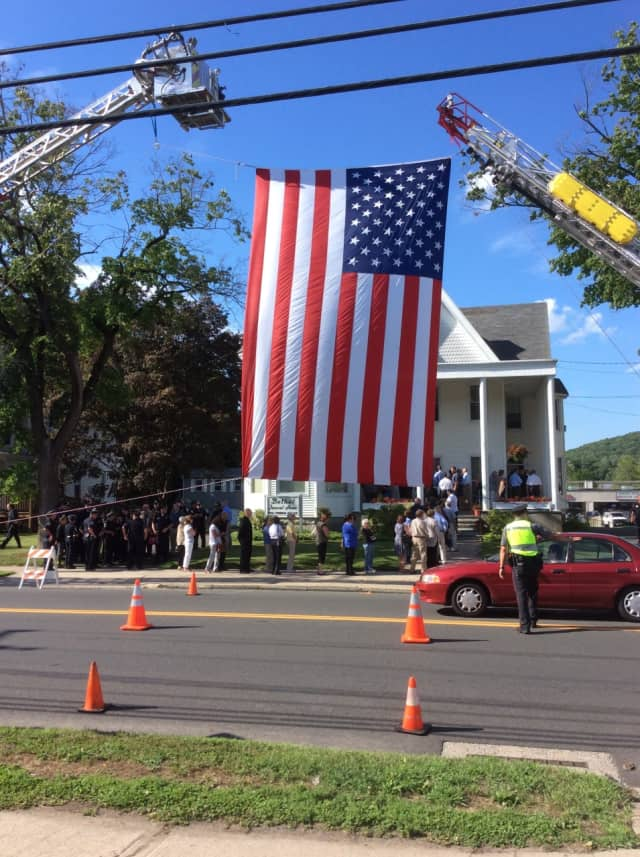 A U.S. flag hangs across the road at calling hours last Friday for retired police Lt. Kevin Kelly at the Bethel Funeral Home.