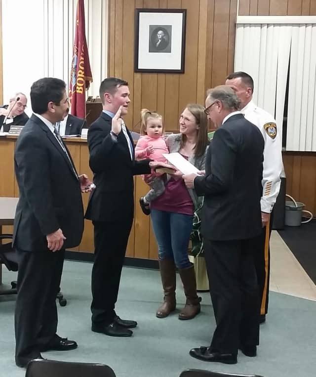 John DeCamp Jr. is sworn in as wife, Rachel, and their daughter, Riley, look on.