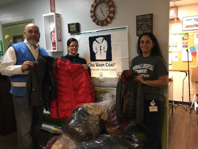 Frank Concepcion, director of operations for The Open Door Shelter in Norwalk, welcomes the delivery of donated coats from Norwalk Radiology employees Kelly Turnage, of Hamden, and Jessica Solano, of Stratford, Oct. 21, 2016.