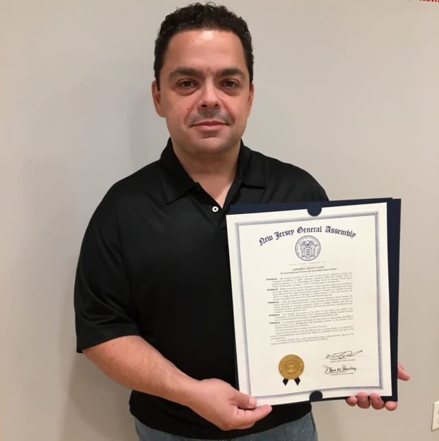 Chuck Anania, owner of Roof4Roof, holds a resolution he received for his efforts to help the community.