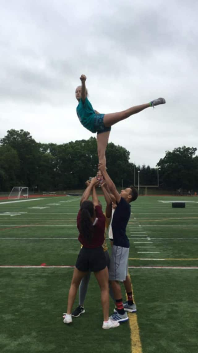 The Norwalk High School cheerleaders are raising money to attend a National Cheerleading Association summer camp.