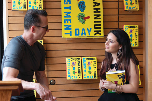 "Danielle Renda speaks with best-selling author Chuck Palahniuk at Greenlight Bookstore in Brooklyn, while he signs her copy of ""Adjustment Day,"" Palahniuk's newest novel. Photograph by Elijah Riess."