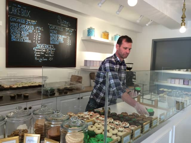 Co-owner Robert Byrnes arranges cupcakes for sale at the new location of Cake Box in Westport.