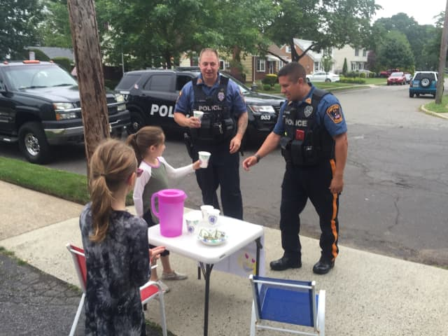 Fair Lawn police officers Tim Ammann, left, and Luis Vazquez say their day was made by Yocheved and Ahuva's lemonade stand.