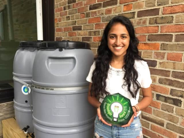 Greenlight Award Competition winner Rachel Joseph of Somers High School holding her Greenlight Award next to her rain barrels in the Primrose Elementary School garden.