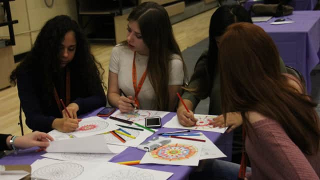 Dumont High School students unwind stress with coloring books.