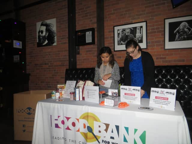 Kristina Magana, left, and Madeline Sulla of the Food Bank For Westchester collected non-perishable goods on Wednesday night during a holiday concert at Garcia's at The Capitol Theatre in Port Chester. The Cap plans more charity events next week.