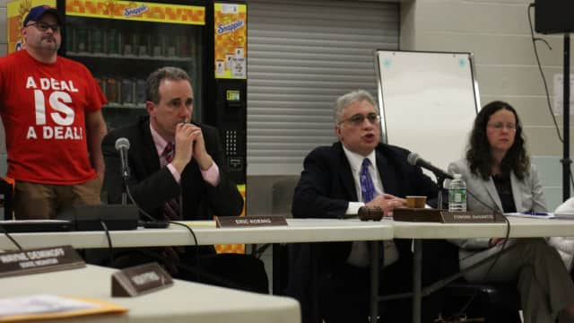 Superintendent Eric Koenig looks on as Board of Education President Edmund DeSantis responds to criticisms of the board.