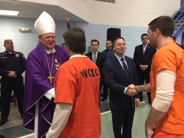 Cardinal Timothy Dolan and County Executive Astorino greet prisoners after the Mass service.