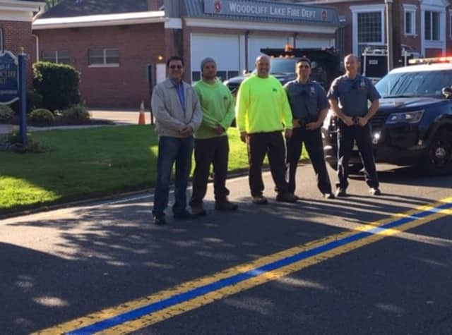 (From left): Woodcliff Lake Council President Corrado Belgiovine, DPW employees David Linko and Ray Blackston, Officers Simon Sherfer and Keith Kalmbach stand proudly on blue line on Pascack Road in front of Borough Hall.