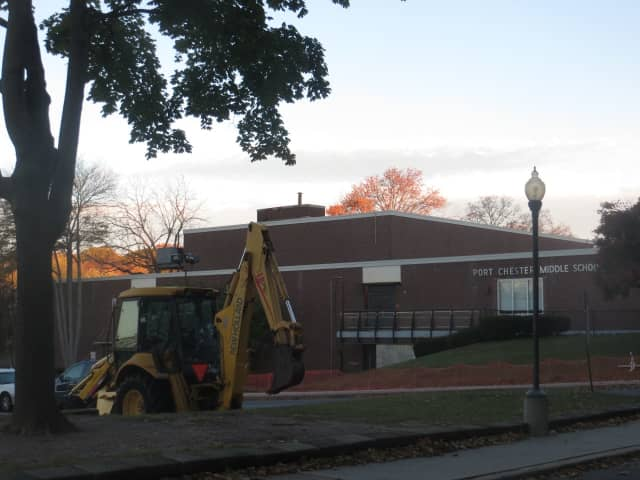 A bulldozer and temporary orange fences surround Port Chester Middle School and the Port Chester-Rye Union Free School District offices on Tuesday Oct. 31 after a concrete panel collapsed smashing windows at the school on Oct. 26, prompting repairs.