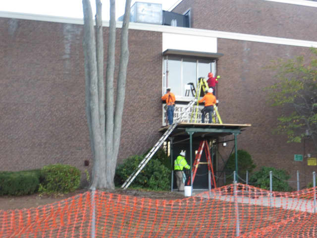 Workers outside the Board of Education and District office entrance of Port Chester Rye Union Free District on Tuesday Oct. 31. Ongoing emergency repairs have kept the offices and Port Chester Middle School closed since Friday.