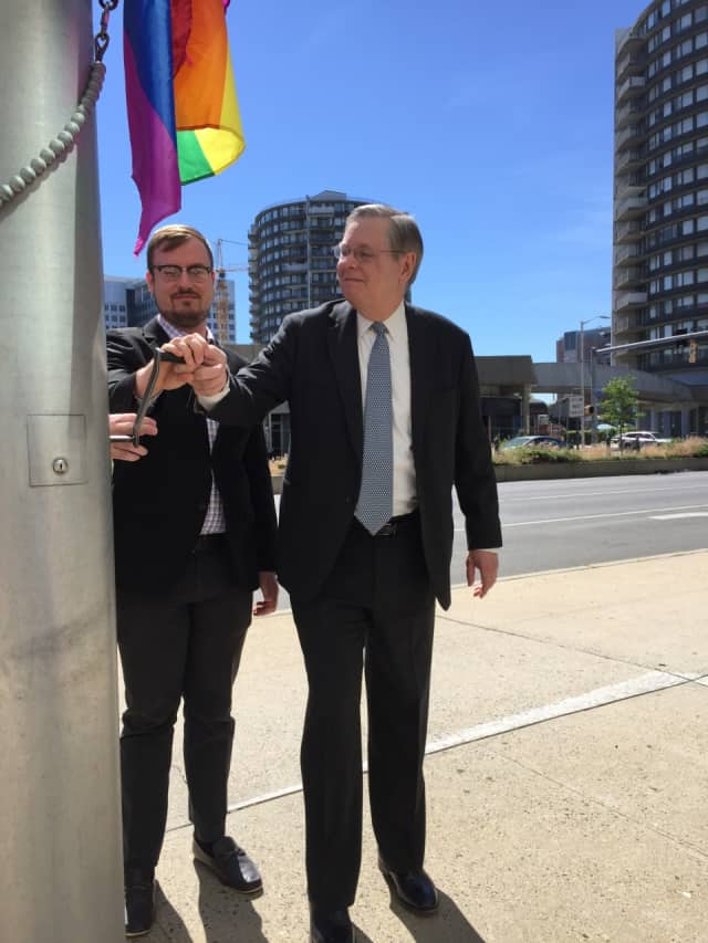 Stamford Mayor David Martin raises the pride flag outside the government center on Wednesday.
