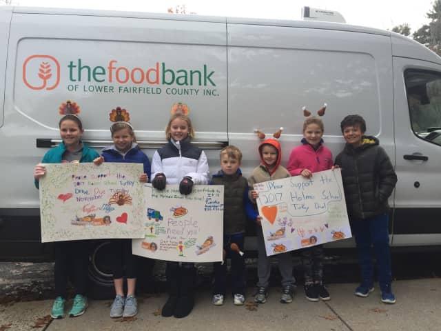 Holmes School students Chloe Adams, Meggie Moles, Shea Ward, Henry Baruch, Luke Firgeleski, Kate Firgeleski and Jake Miller welcomed The Food Bank truck in the school's parking lot.