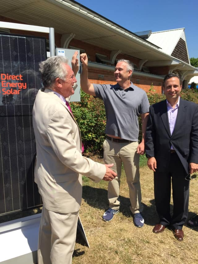 Norwalk Mayor Harry Rilling flips a ceremonial switch on a solar array Wednesday morning along with state Sen. Bob Duff.