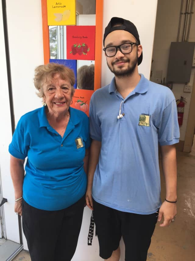 Anne Borges and Kyle Kaplan, employees of Calfe' Mu at Calf Pasture Beach, pose for a photo Wednesday. Borges and Kaplan serve up cool ice cream and beverages to beachgoers.