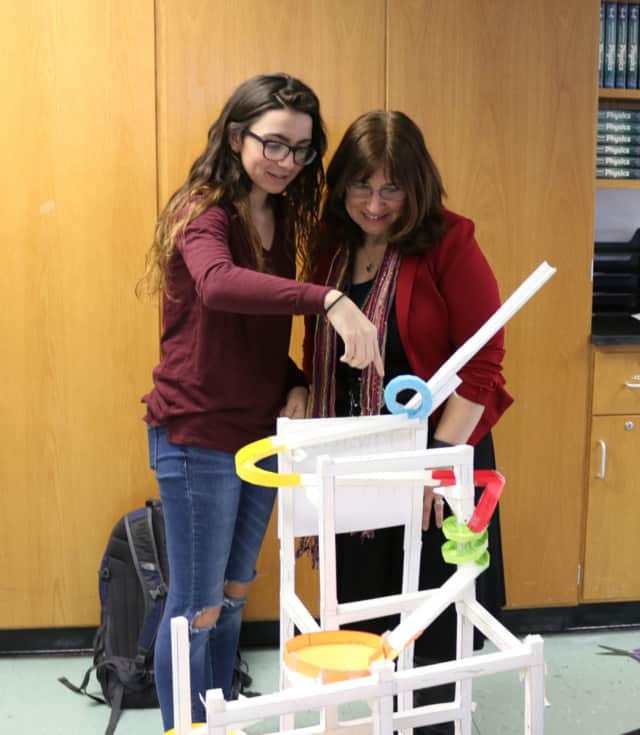 A Lakeland High School student explains the paper roller coaster recently built as a physics project.