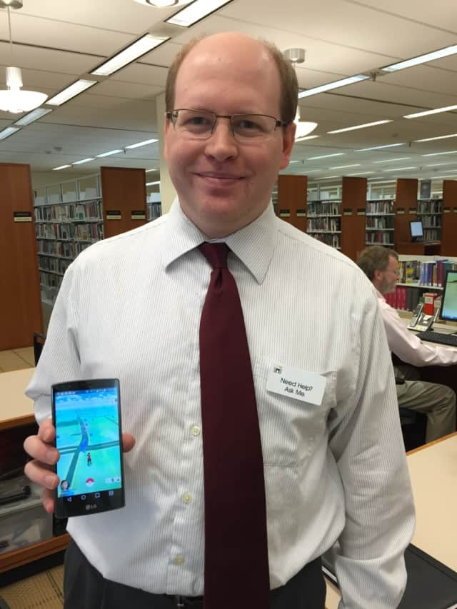 Ferguson Library's Digital Librarian Frank Skornia holds up his phone, showing the viral Pokémon Go app.