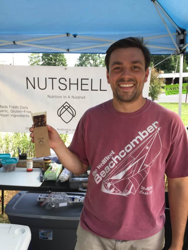 Will D'Agostino holds one of his healthy nut bars at the Wilton Farmers Market on Wednesday.