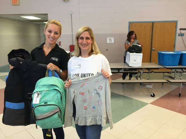 Nicole Granskog and Tessi Ruggeri of the United Way of Western Connecticut hold up school supplies donated to children in need on Tuesday.