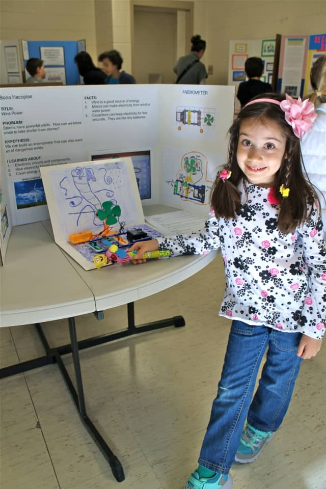 A student showing off her project at the science fair.