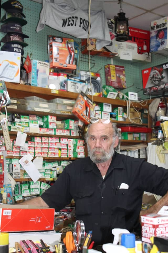 Robert Sconfienza in his shop with a military display behind him.