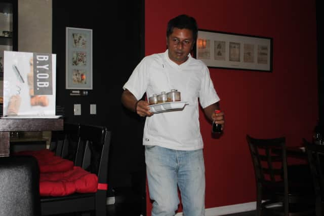 Prashanta Tuladhar brings homemade table sauces to patrons at his cousin Jamphel Dorjee's restaurant.