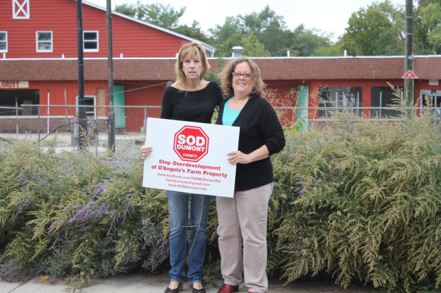 Lili Binney and Rachel Bunin hold their sign in front of D'Angelo Farm, which will be developed.