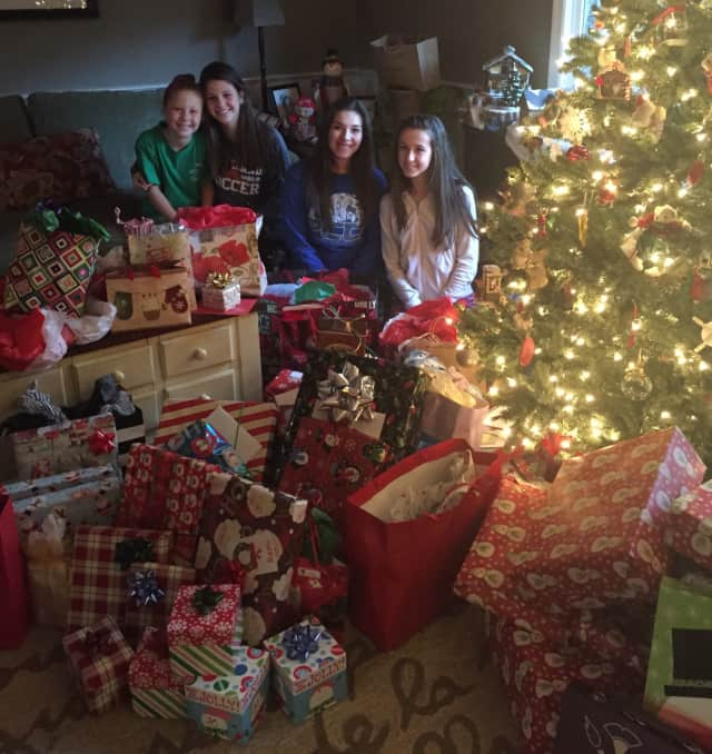 Remi Presky, surrounded by donated gifts, spends Christmas with the Sheehan family.