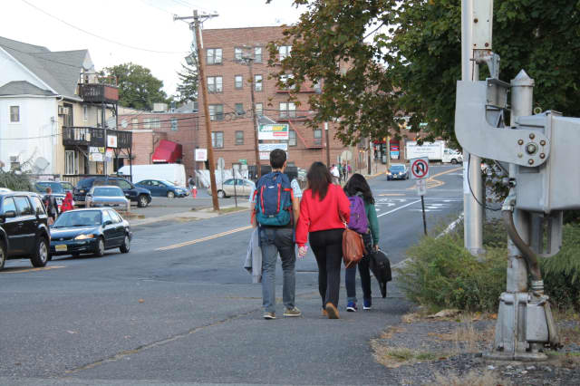 Students exit and walk along a busy roadway near Bergenfield High School.