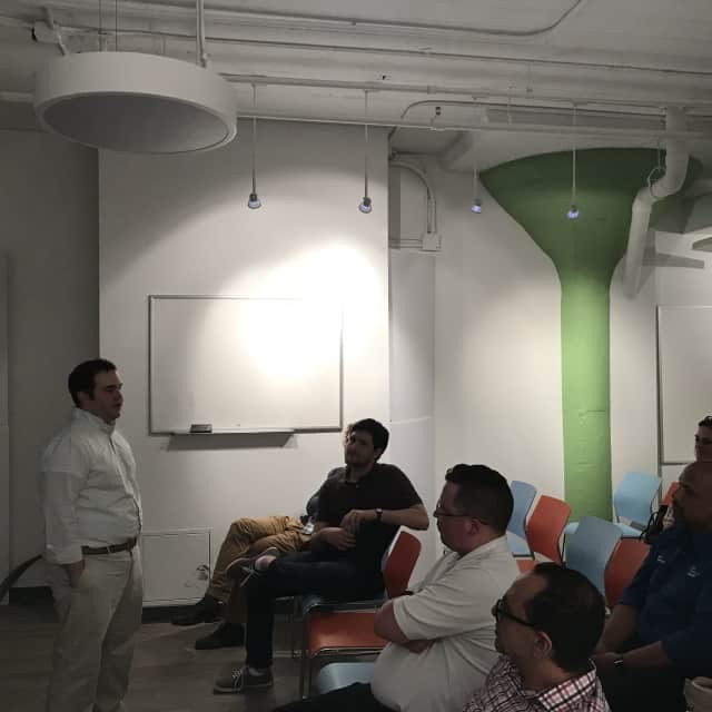 Michael McClure (standing) shares coding insights during one of Crashcode's HackNight events in Stamford.