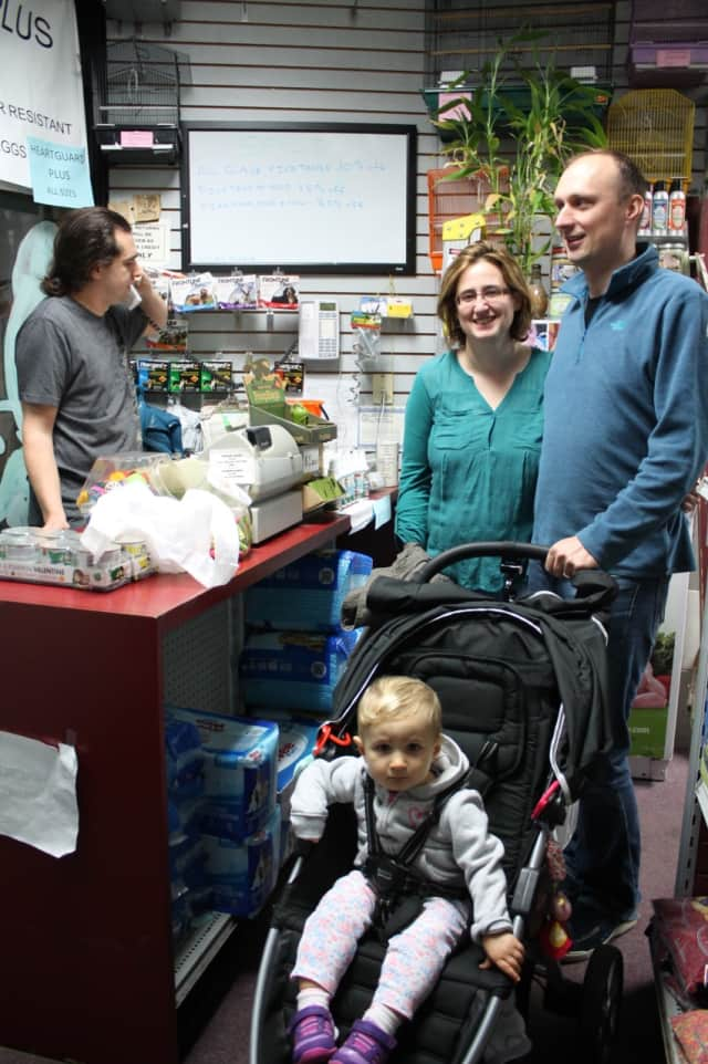 Fort Lee Pet Shop owner Tom Piper, left, with customers in his shop before it closes Nov. 28.