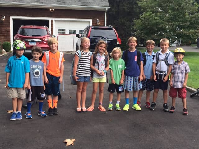 Students wait at the Echo Valley bus stop for the first day of school at Holmes Elementary School in Darien.