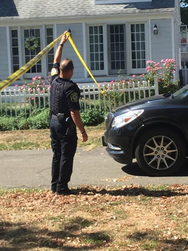 An officer lets a car pull into the Lordship neighborhood in Stratford where the shooting occurred on Sept. 14.