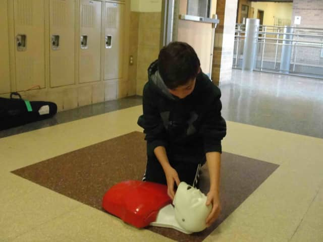 An eighth-grader at Irvington Middle School performs CPR on a mannequin.